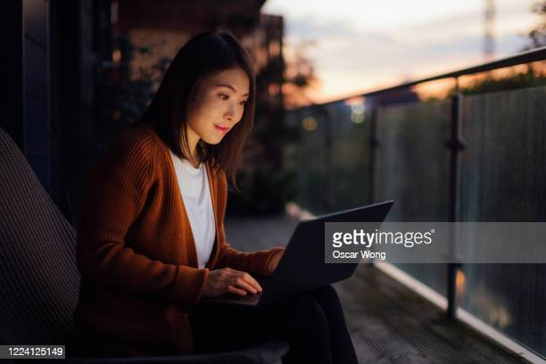 young woman working with laptop at night - working stock pictures, royalty-free photos & images
