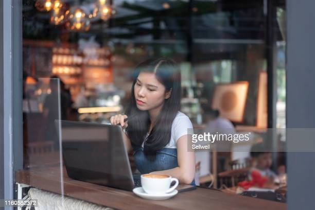 young woman working with laptop in the cafe - internet cafe stock pictures, royalty-free photos & images