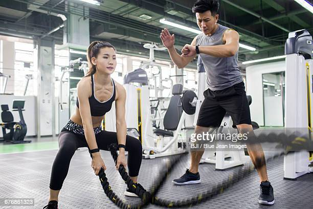 young woman working with trainer at gym - asian female bodybuilder stock photos and pictures
