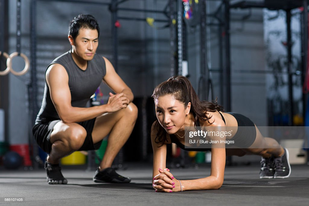 Young woman working with trainer in gym : Stock Photo
