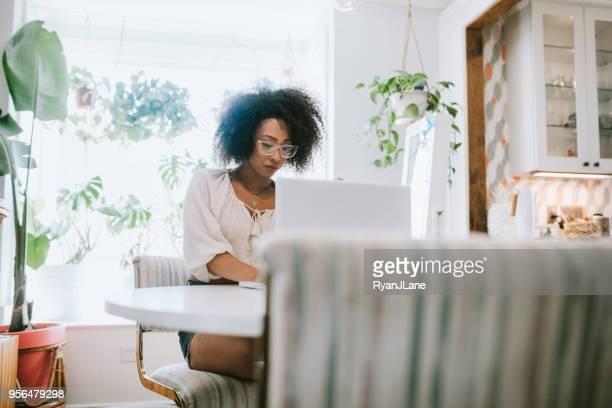 een jonge vrouw werken vanuit huis op haar laptop - afro amerikaanse etniciteit stockfoto's en -beelden