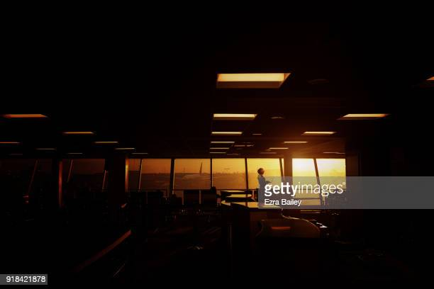Young woman works on a laptop in an airport at sunset.