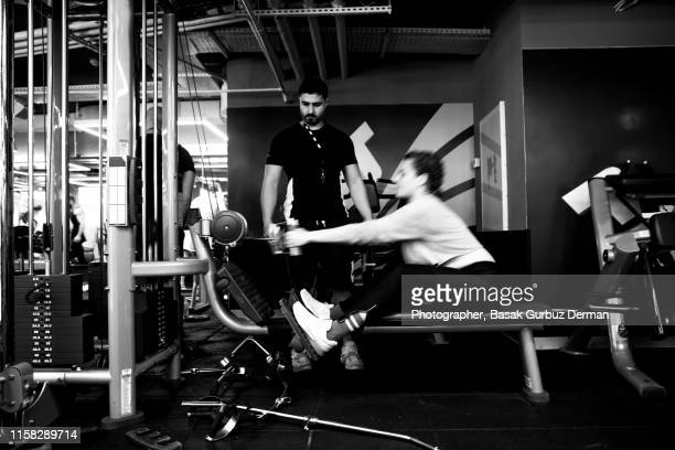 A young woman works out on a rowing machine at the gym by the help of a male personal trainer