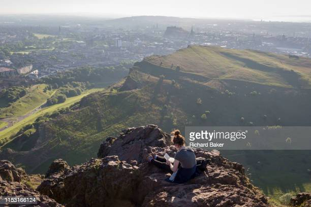 A young woman works with a notebook in summer evening sunshine on the summit of Arthur's Seat in Holyrood Park overlooking the city of Edinburgh on...