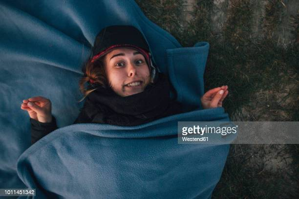 Young woman wrapped in a blanket lying in grass