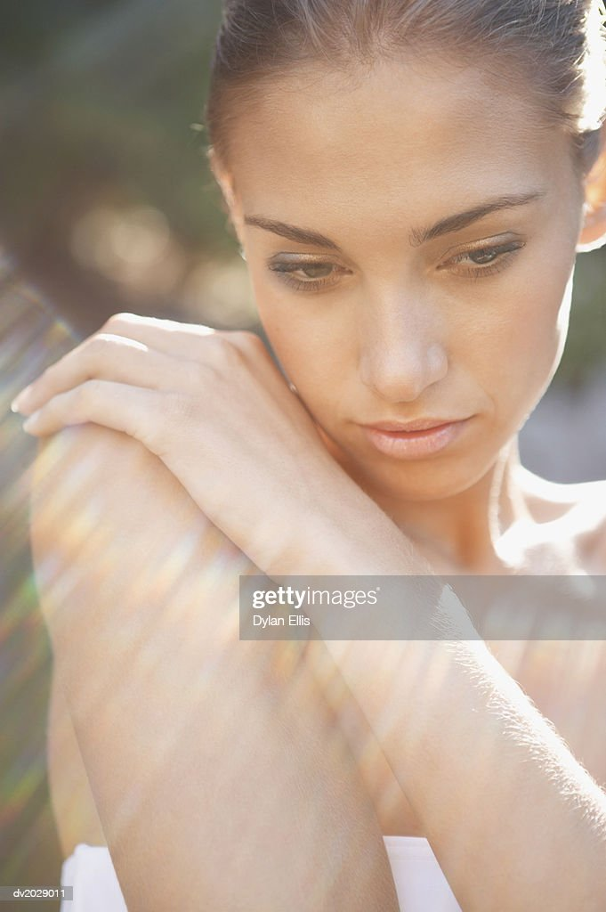 Young Woman Wrapped in a Towel and Looking Down : Stock Photo