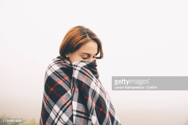 young woman wrapped in blanket during foggy weather - avvolto in una coperta foto e immagini stock