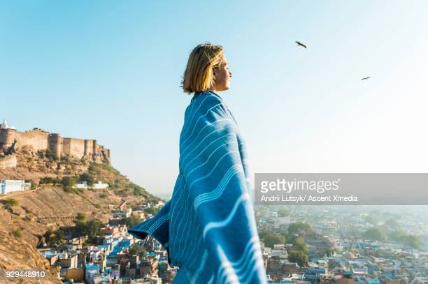 Young woman wrapped in blanket looks over city