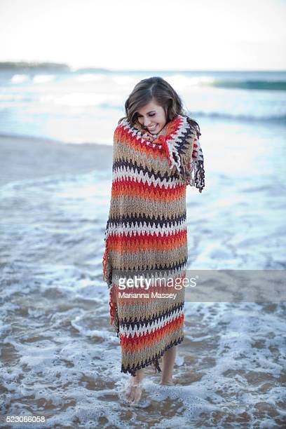 Young woman wrapped in blanket on beach