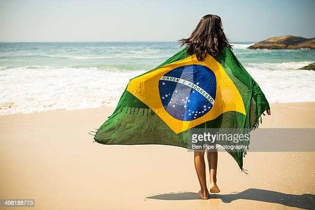 Young woman wrapped in Brazilian flag, Arpoador beach, Rio De Janeiro, Brazil