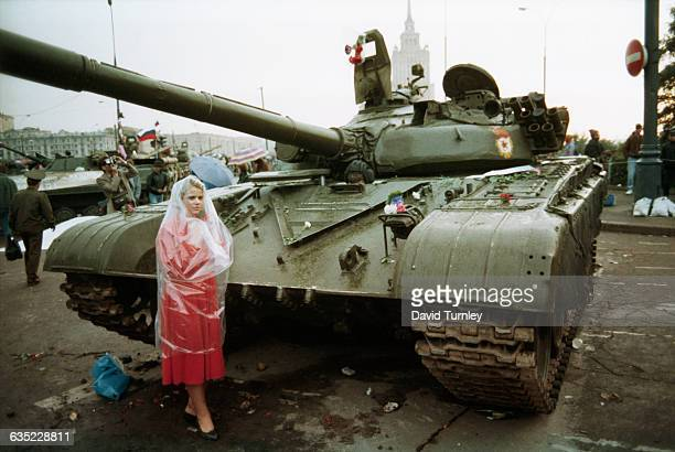 Young woman wrapped in plastic against the rain stands in Red Square, next to a Soviet tank decorated with flowers. Citizens helped barricade the...