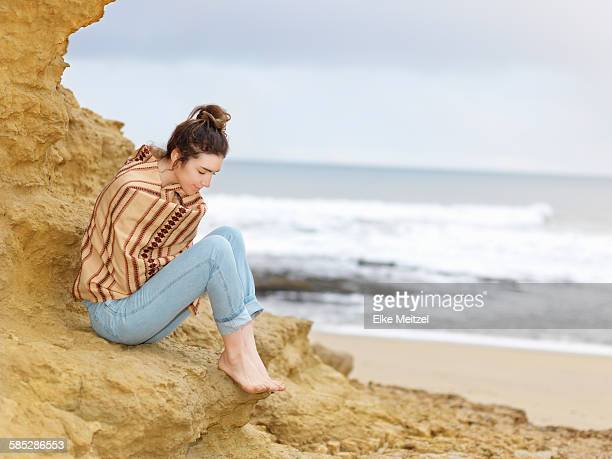 Young woman wrapped in shawl sitting on cliffside, Point Addis, Anglesea, Victoria, Australia