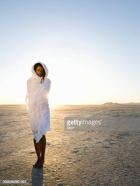 Young woman wrapped in sheet in desert, portrait