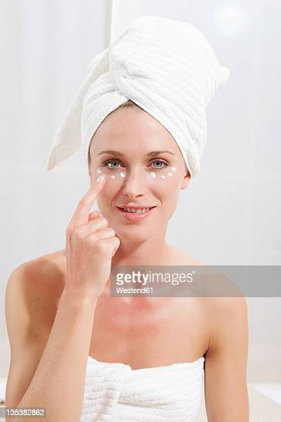Young woman wrapped in towel appyling face cream