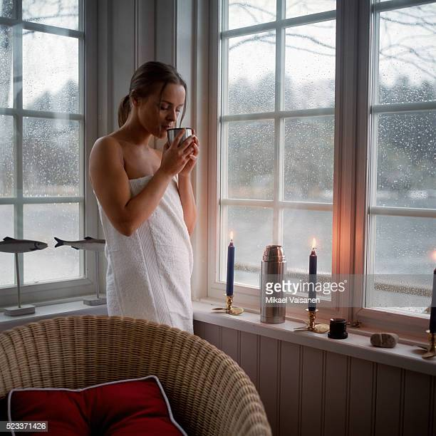 Young Woman Wrapped in Towel Drinking from Thermos Flask