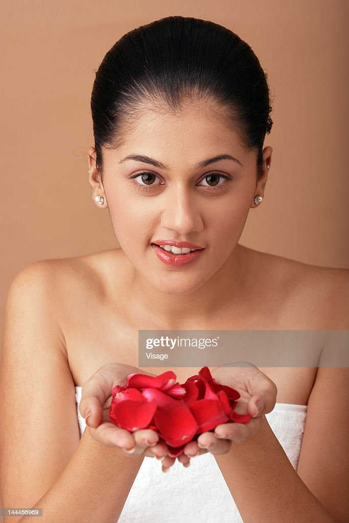 Young woman wrapped in towel holding rose petals : Stock Photo