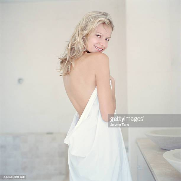 Young woman wrapped in towel looking over shoulder, portrait