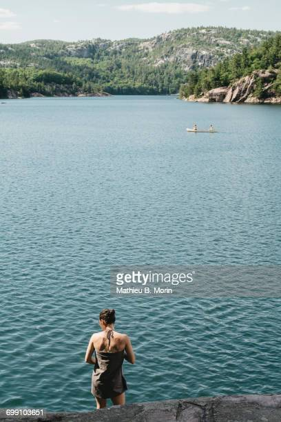 young woman wrapped in towel while a canoe is crossing the lake - sudbury canada stock photos and pictures