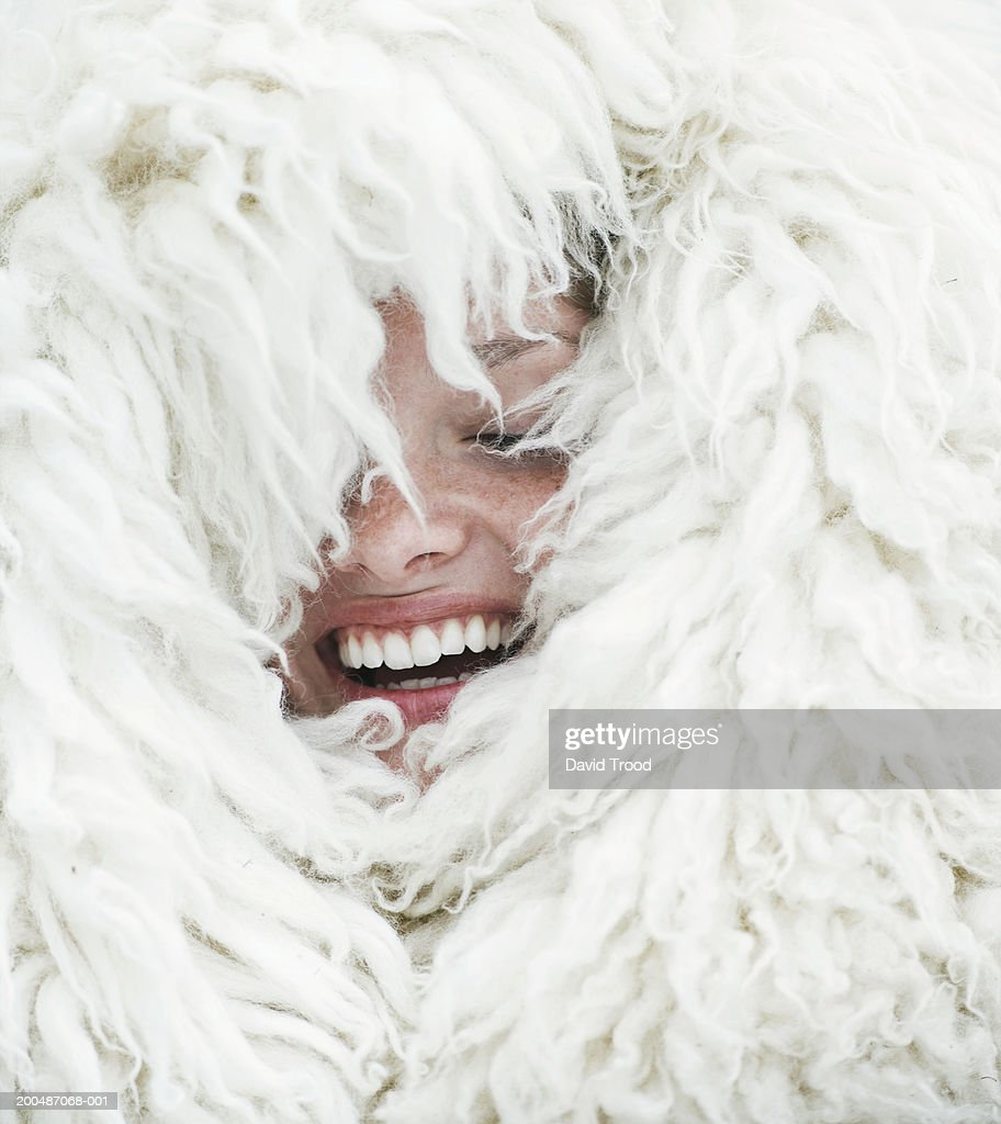 Young woman wrapped in wool blanket, eyes closed, laughing, close-up : Stock Photo