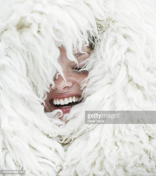 young woman wrapped in wool blanket, eyes closed, laughing, close-up - avvolto in una coperta foto e immagini stock