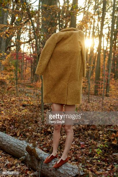 Young woman wrapped up in a gold jacket standing in the woods.