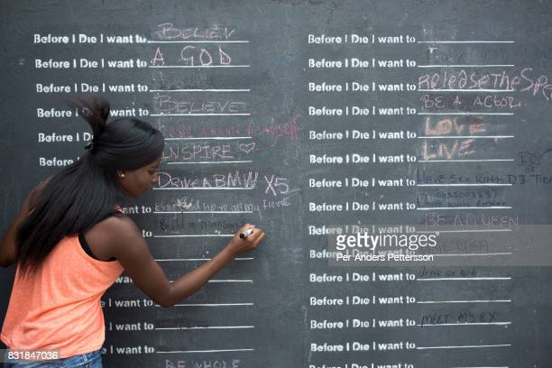 A young woman writes hew wishes on a wall in Maboneng district on March 15 2016 in downtown Johannesburg South Africa A former derelict industrial...