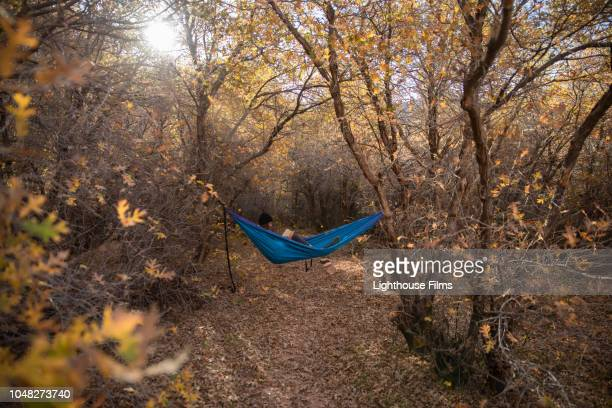 Young woman writes in journal while relaxing in a hammock surrounded by Autumn leaves  in a wooded clearing of Moab, Utah.