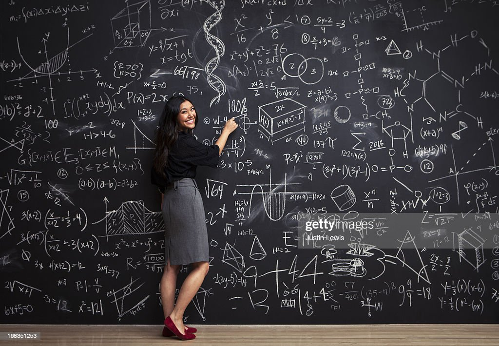 Young woman writes math equations on chalkboard : Stock Photo