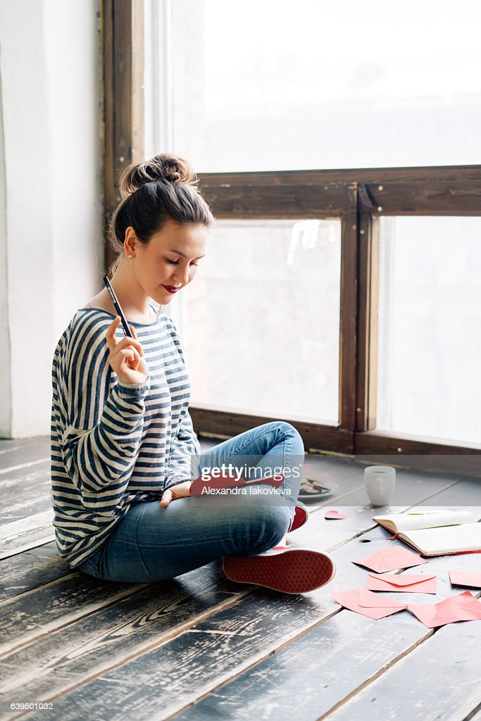 Young woman writing a valentine card : Stock Photo