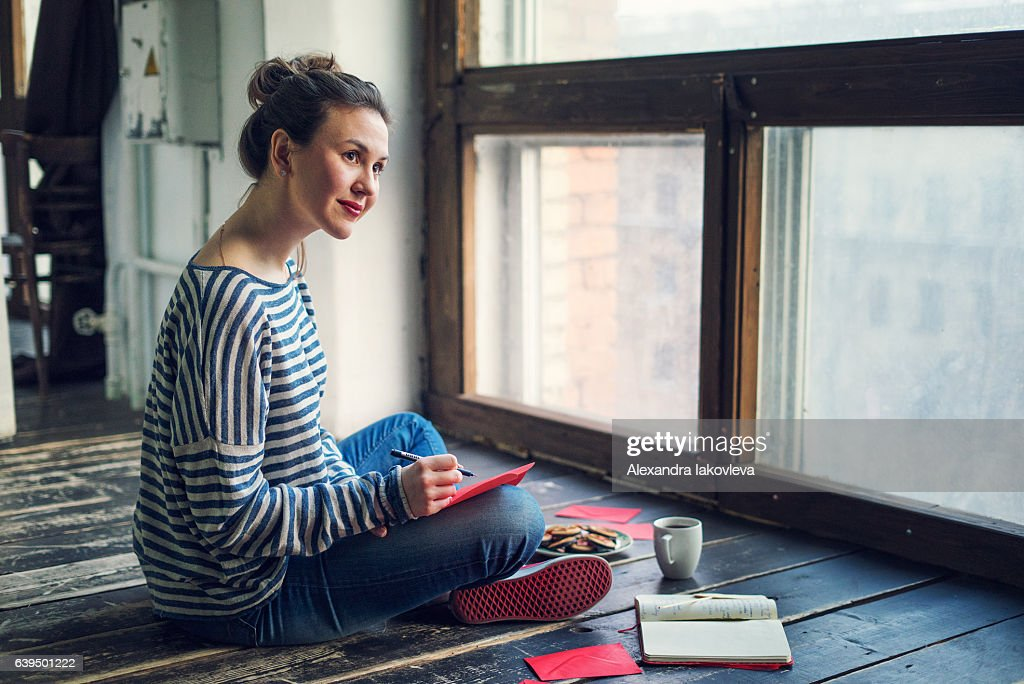 Young woman writing a valentine card : Stock-Foto