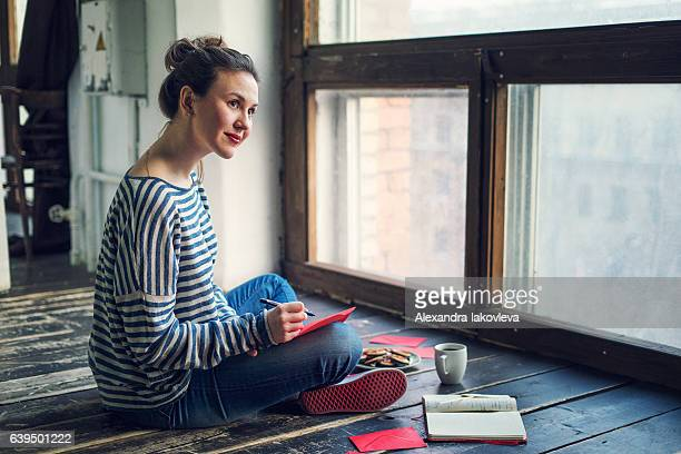 young woman writing a valentine card - bericht stockfoto's en -beelden