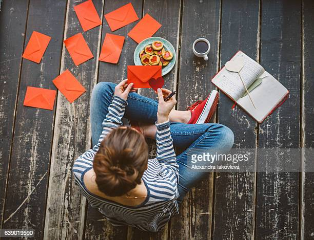 young woman writing a valentine card - top view - valentine's day holiday stock pictures, royalty-free photos & images
