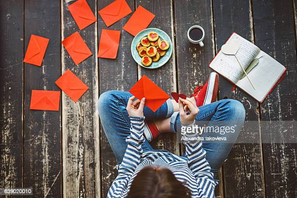 Young woman writing a valentine card - top view