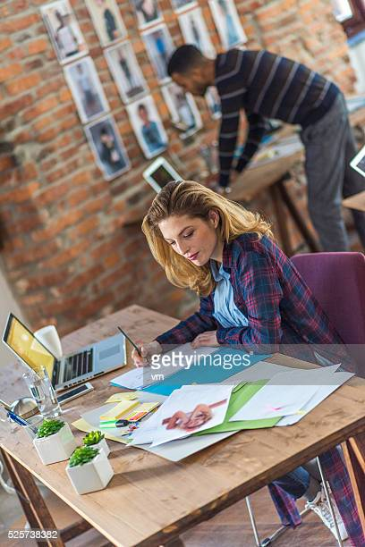 Young woman writing and using laptop in the office