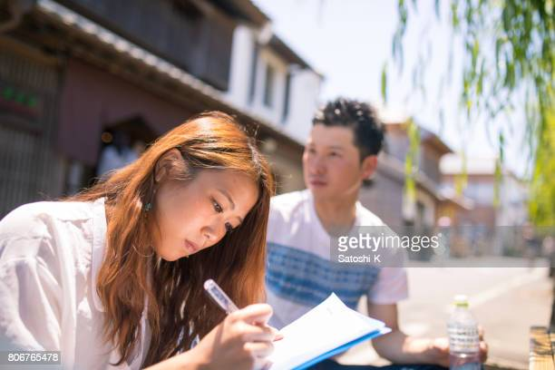 Young woman writing document on street