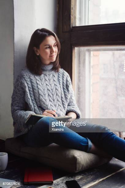 young woman writing in a diary by the window - diary stock pictures, royalty-free photos & images
