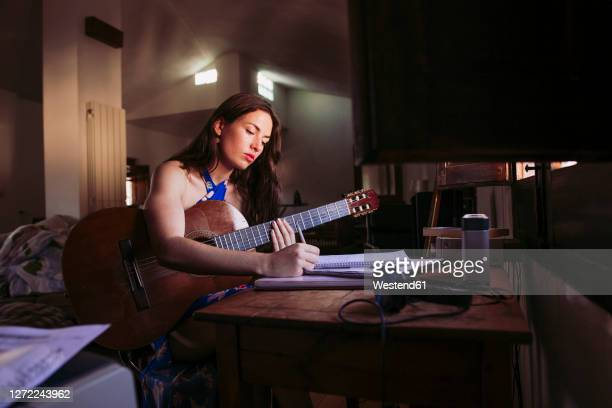young woman writing in book while practicing guitar at home - シンガーソングライター ストックフォトと画像