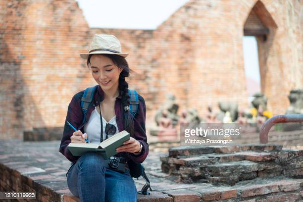 young woman writing in diary - authors ストックフォトと画像