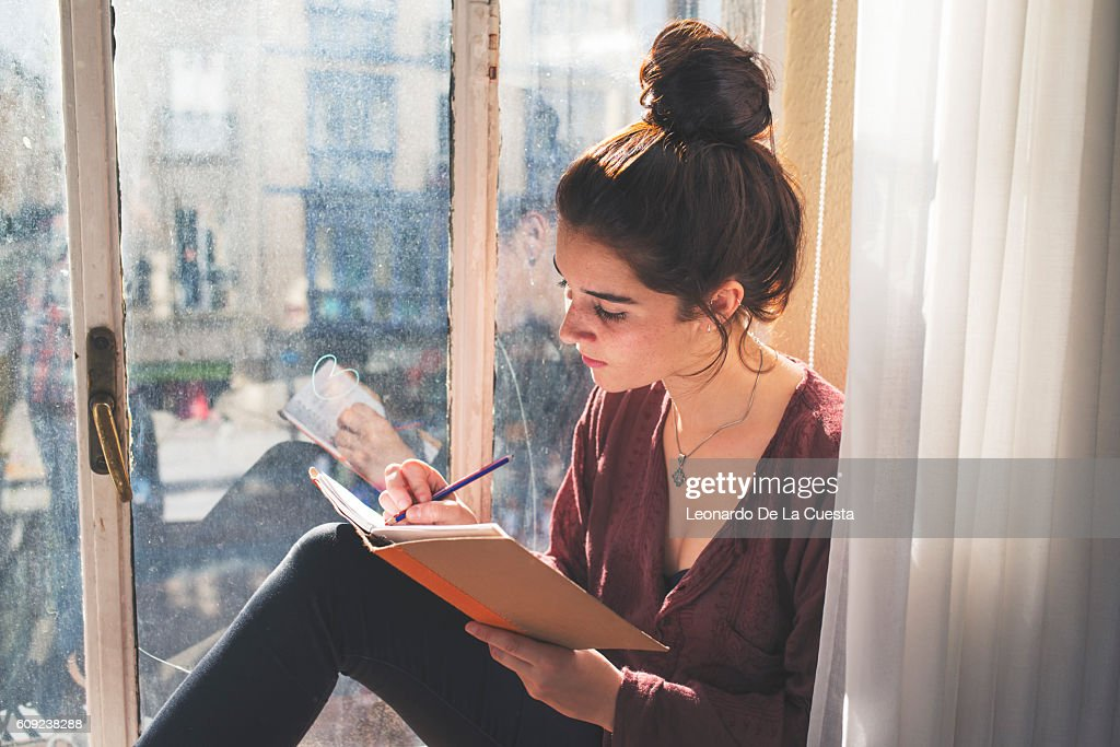 Young woman writes daily next to the window.