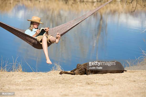 Young woman writing in journal while resting in hammock in Bishop, CA.