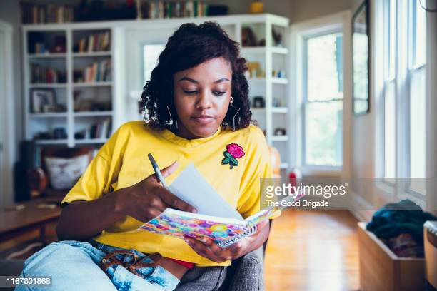 young woman writing in notebook - diary stock pictures, royalty-free photos & images