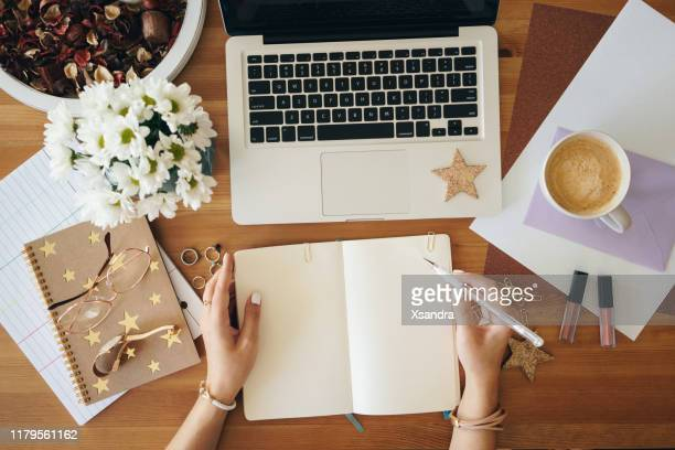 young woman writing notes and working on a laptop - flat lay stock pictures, royalty-free photos & images