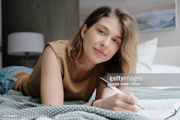 young woman writing on bed - showus stock pictures, royalty-free photos & images