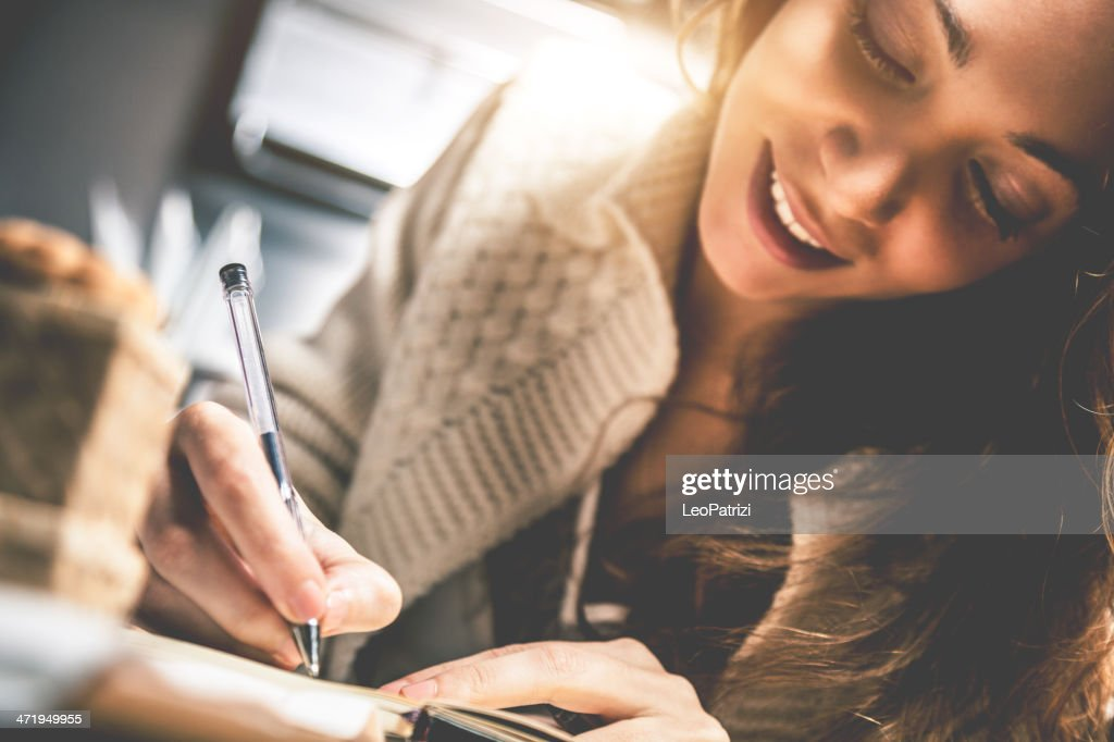 Young woman writing on diary : Stock Photo