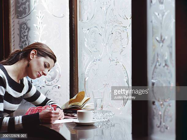 young woman writing postcard in pub - correspondence stock pictures, royalty-free photos & images