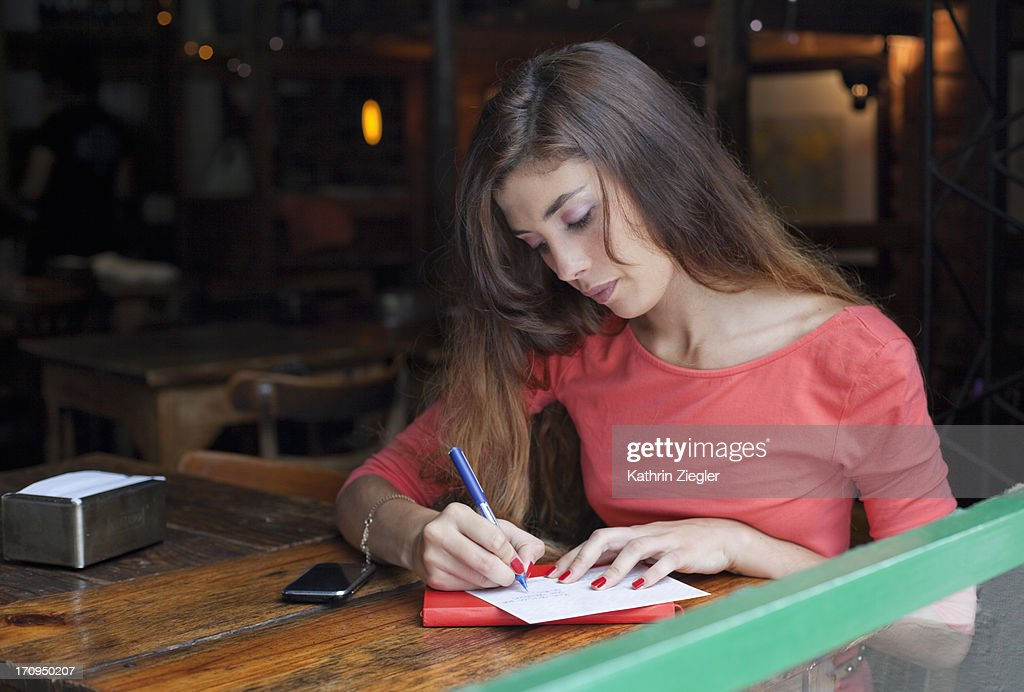 young woman writing postcards at a café : Stock Photo