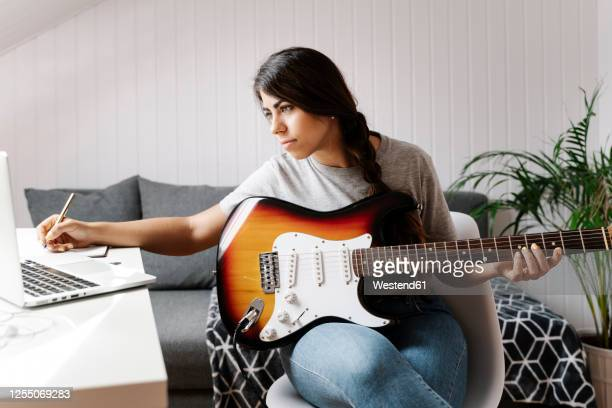 young woman writing while using laptop and electric guitar at home - guitarist stock pictures, royalty-free photos & images