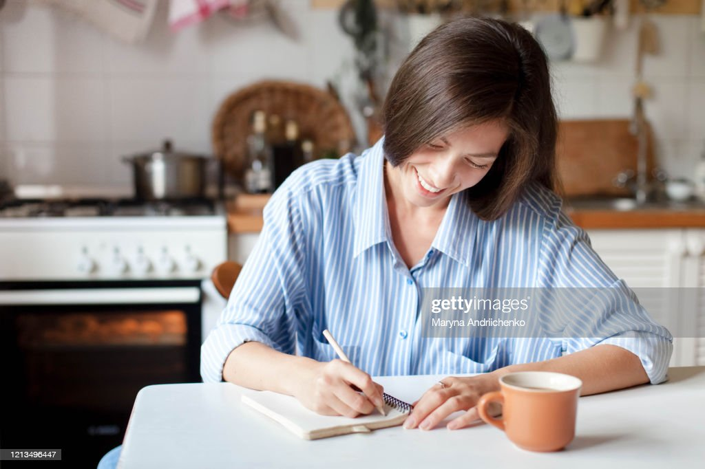 Young woman writting notes in paper notebook. Happy girl sitting at table with cup of coffee : Stock Photo