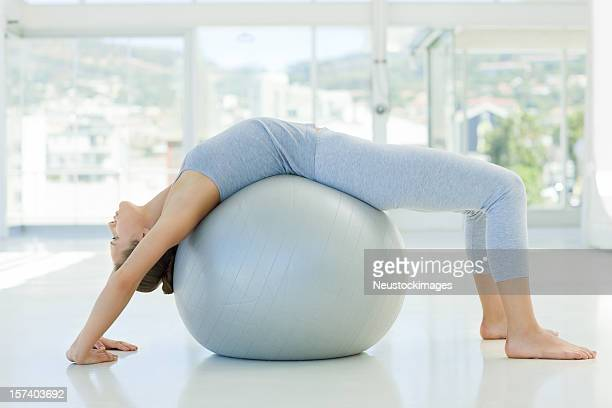 Young woman xercising on fitness ball
