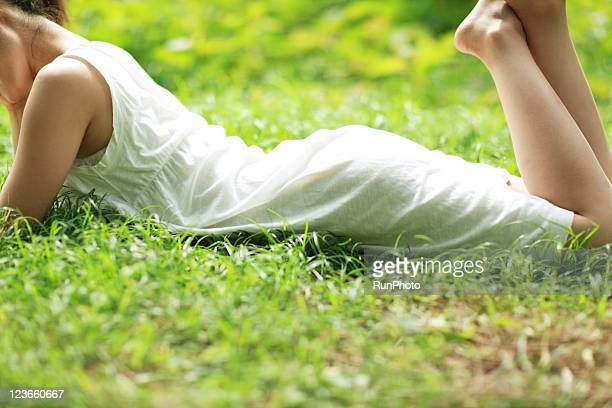 young woman ?ying in the grass - newhealth stock pictures, royalty-free photos & images